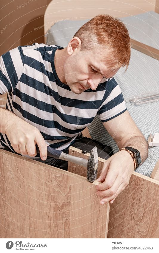 Good looking concentrated caucasian man in striped t-shirt assembles furniture with a hammer. Furniture assembly, repair, moving. Vertical shot good looking