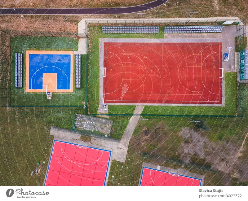 Colorful basketball, volleyball and soccer grounds. A red ,orange and blue colored outdoor sports grounds for basketball, handball and soccer from above.