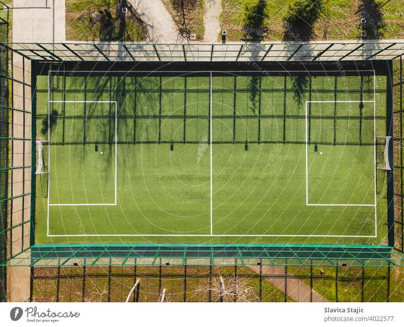 Drone View Of Street Soccer Court. Outdoor sport ground with green surface for playing football  or soccer  in urban area, detail, drone view activity