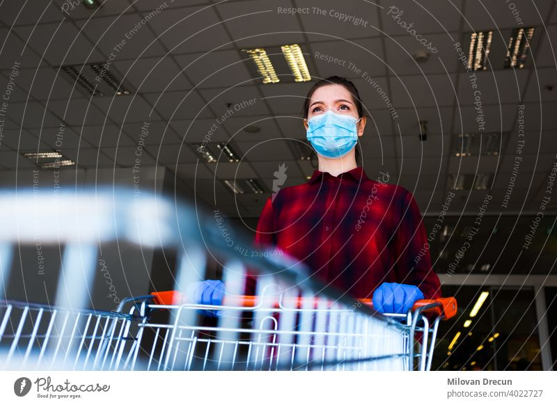 Worried and anxious caucasian woman wearing protective surgical face mask and latex gloves anxiety buying cart checklist corona coronavirus covid-19 crisis