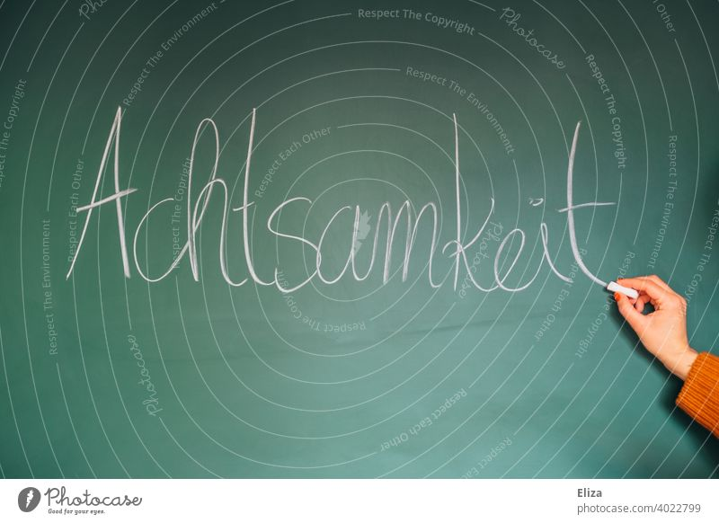 Hand writes the word mindfulness on a blackboard attentiveness Write Word well-being Meditation relaxation Buddhism Consciousness Happy stress reduction