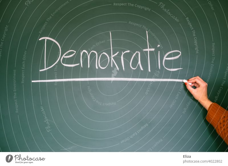 Democracy - word written on blackboard Blackboard authored Word Democratic policy Elections Select constitutional law Fairness Freedom politically state