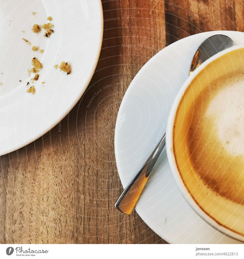 Plate with crumbs and a half full cup of latte Coffee Coffee break Coffee cup To have a coffee Edge of a plate Spoon White Wood Wooden table Foam Empty Eaten