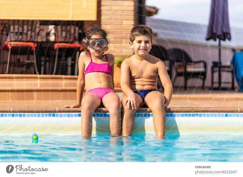 Two funny kids on a poolside active activity adorable aqua blue boy brother caucasian child childhood children cute edge family friends friendship girl glasses