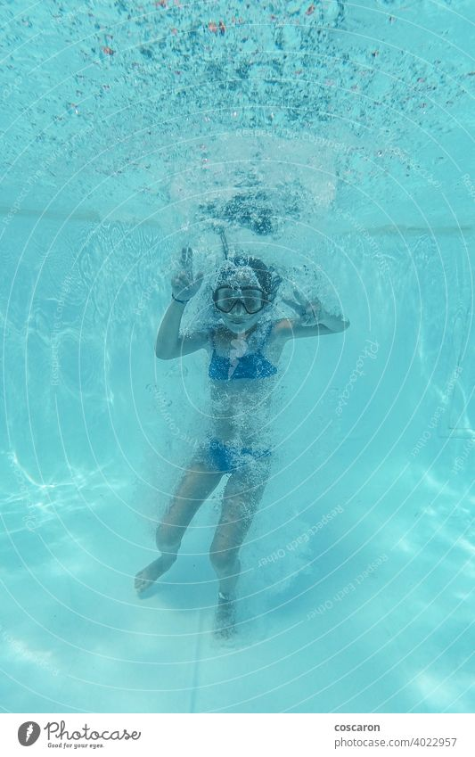 Little girl jumping into a pool and diving action activity aqua park aquatic blue bubbles child clear concept copy space deep down face fitness foam fun glasses
