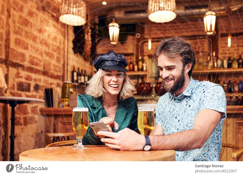 Caucasian couple having a drink at a bar. adult woman people happy female lifestyle two caucasian beautiful together smile love joy boyfriend indoors romance