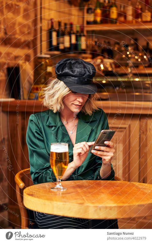 Woman looking at her smartphone at a bar. couple adult woman happy female restaurant lifestyle caucasian beautiful happiness drink fun joy romantic indoors