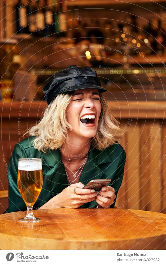 Woman looking at her smartphone at a bar. couple adult woman happy female restaurant lifestyle caucasian beautiful happiness drink smile fun love joy
