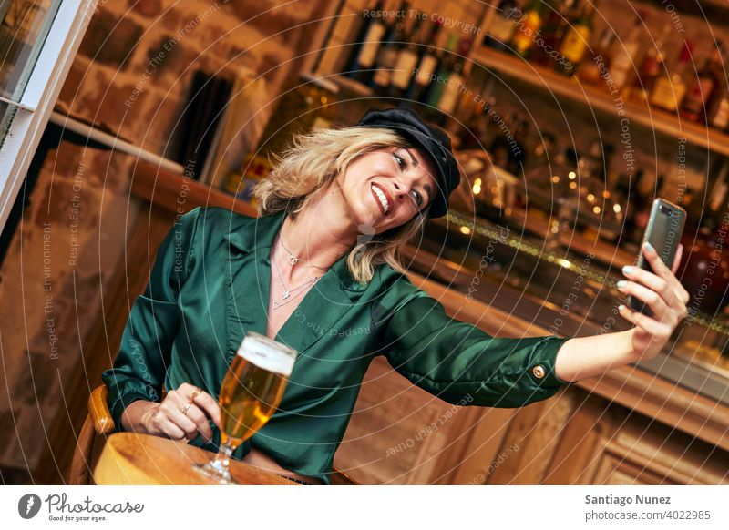 Woman taking a selfie at a bar. couple adult woman happy female restaurant lifestyle caucasian beautiful happiness drink smile fun love joy celebration dating