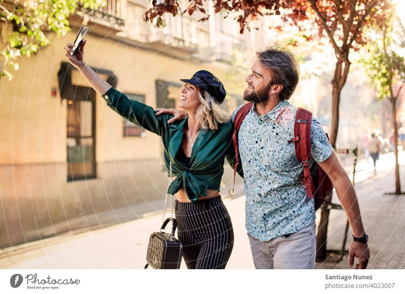 Couple walking on street taking a selfie couple adult woman people happy female lifestyle two caucasian beautiful happiness together drink smile fun love joy