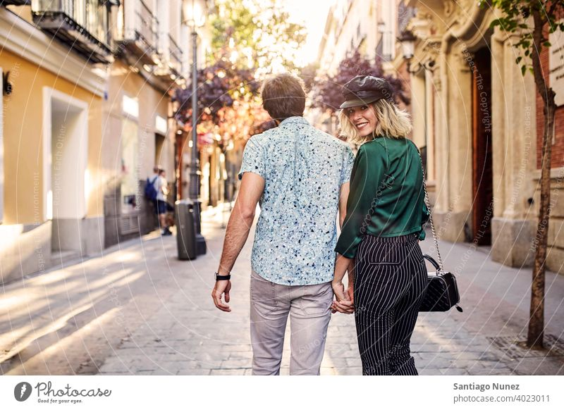 Couple walking on street away from camera. couple adult woman people happy female lifestyle two caucasian beautiful happiness together drink smile fun love joy