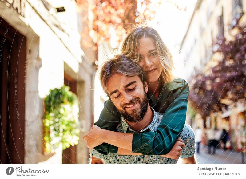 Woman piggyback on man on street. couple adult woman people happy female lifestyle two caucasian beautiful happiness together drink smile fun love joy boyfriend