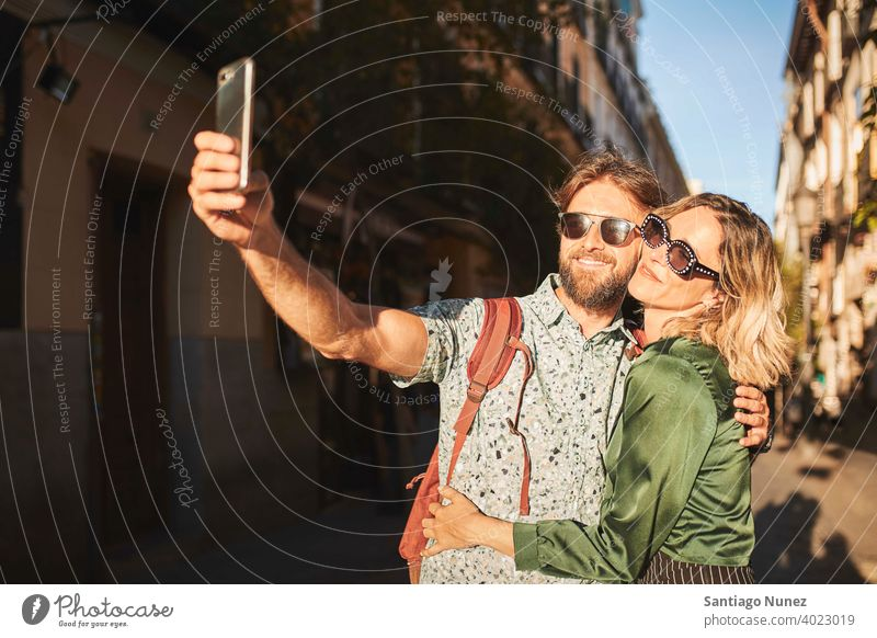 Couple walking on street taking a selfie couple adult woman people happy female lifestyle two caucasian beautiful happiness together smile fun boyfriend dating
