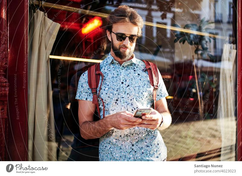 Man looking at his phone on the streets. adult happy lifestyle caucasian happiness smile fun love joy leisure cheerful laughing date smiling enjoyment 30s