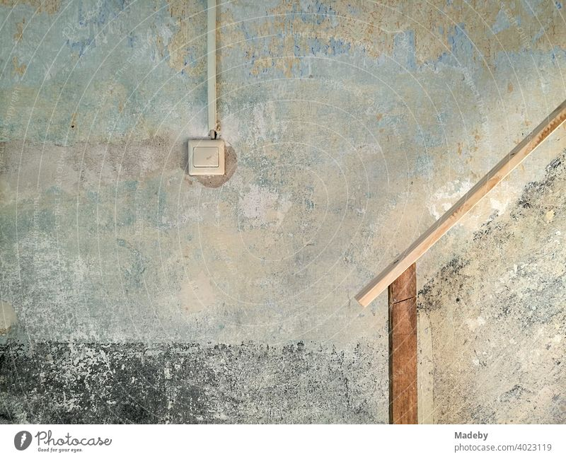 Light switch and improvised staircase railing in a staircase in need of renovation on a farm in Rudersau near Rottenbuch in the district of Weilheim-Schongau in Upper Bavaria
