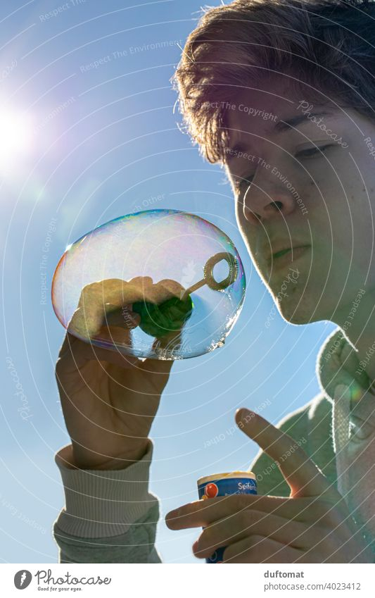 Teen blows bubbles in cold weather Beam of light Boy (child) Soap bubble teenager Dream dream submerged Blow Air Infancy Easy Young man Expectation Joy Flying