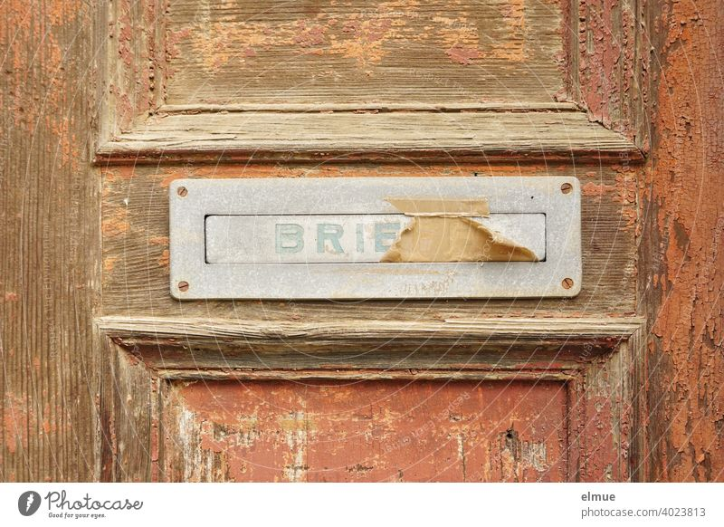"old, pasted mailbox slot with a flap that says ""LETTERS"", made of metal in an old wooden door, where the brown paint is peeling off / write letter / e-mail / mailbox company"