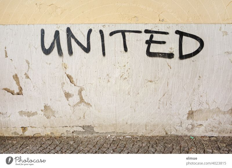 """UNITED"" is written in black capital letters on the gray, old, plastered wall / connected / scrawl. united Wall (building) interconnected Facade Password"