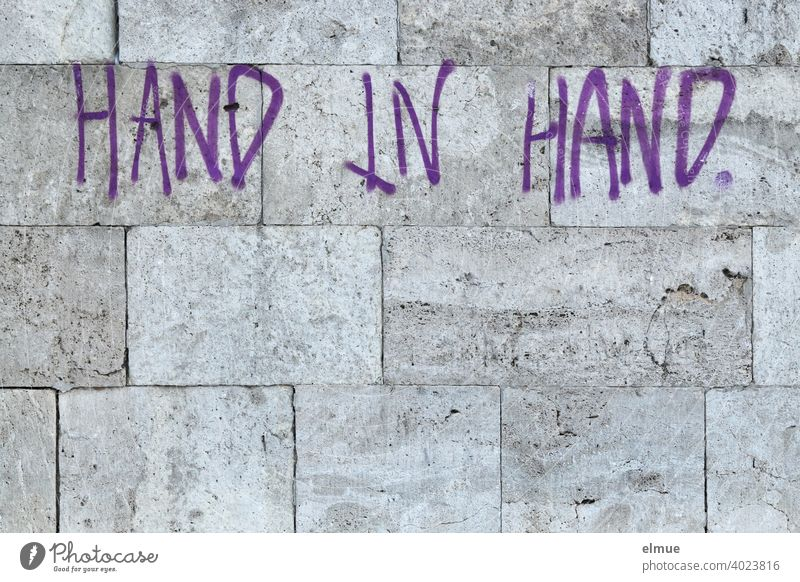 """HAND IN HAND"" is written in purple block letters on the grey natural stone wall / together. Hold hands Wall (building) Facade in common Password Graffito"