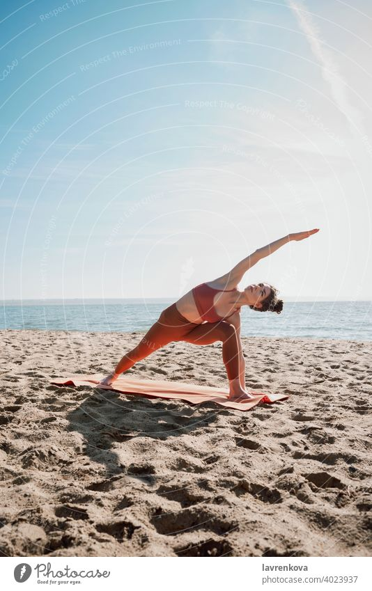 Young female in orange top and leggins practising Extended Side Angle Pose (Utthita Parsvakonasana) woman exercise pose yoga beach young practicing outdoor