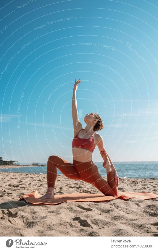 Young female in orange top and leggins practising Crescent Moon Pose (Anjaneyasana Variation)  on a beach in the morning woman exercise pose yoga young