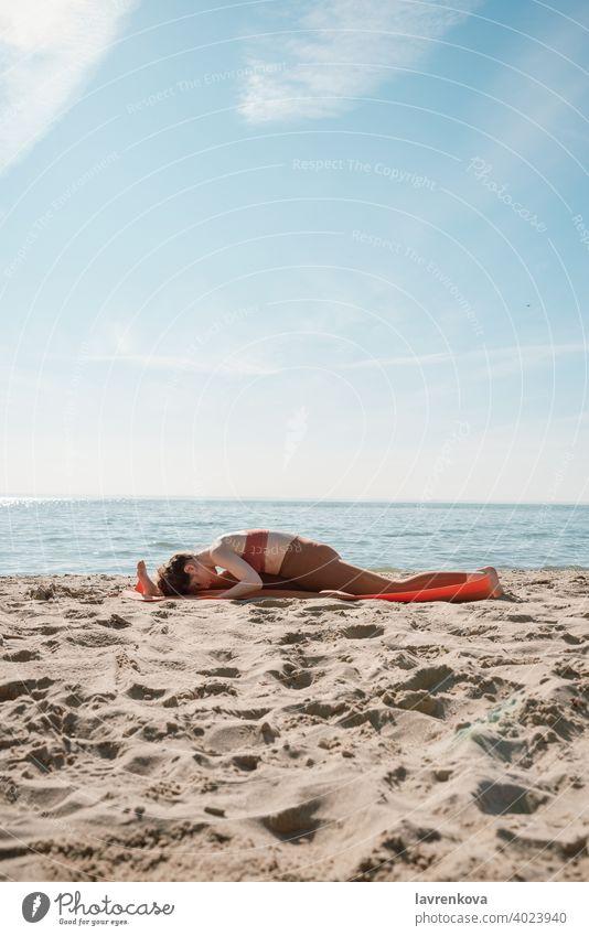 Young female in orange top and leggins practising Yoga split variation (Hanumanasana) on a beach in the morning woman yoga fit training splits sporty leggings