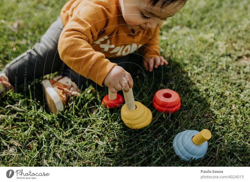 Child playing with toys in the grass Wood wooden Toys 1 - 3 years Caucasian Sit sitting Grass Toddler Human being Infancy Colour photo Playing Day Joy