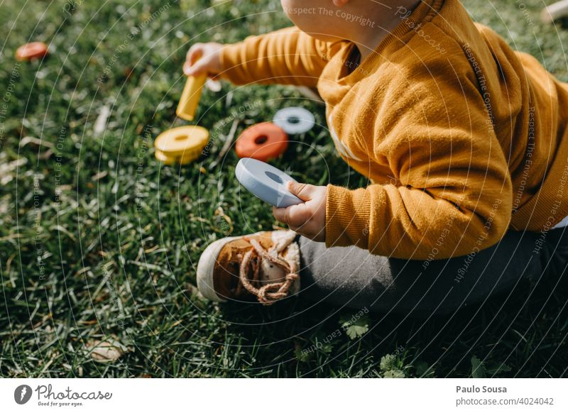 Child playing with toys in the grass childhood Unrecognizable Toys activity joy happy outdoors little unrecognizable kid lifestyle nature Playing Education