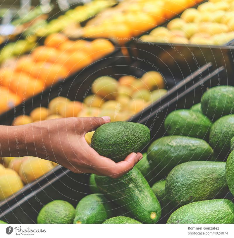 Young Woman Choosing Avocados in Grocery Store. Concept of healthy food, bio, vegetarian, diet. Selective focus. vegetables guacamole ingredients aguacate palta