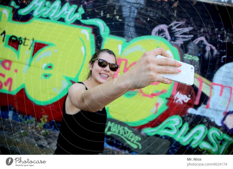 Young woman taking a selfie in front of a graffiti wall smartphone Selfie vanity youthful Self portrait Face Telephone Cellphone mobile phone camera pose