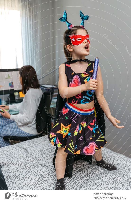 Girl in disguise singing and dancing on the bed while her mother works from home disguised girl funny daughter working in pajamas home work telework