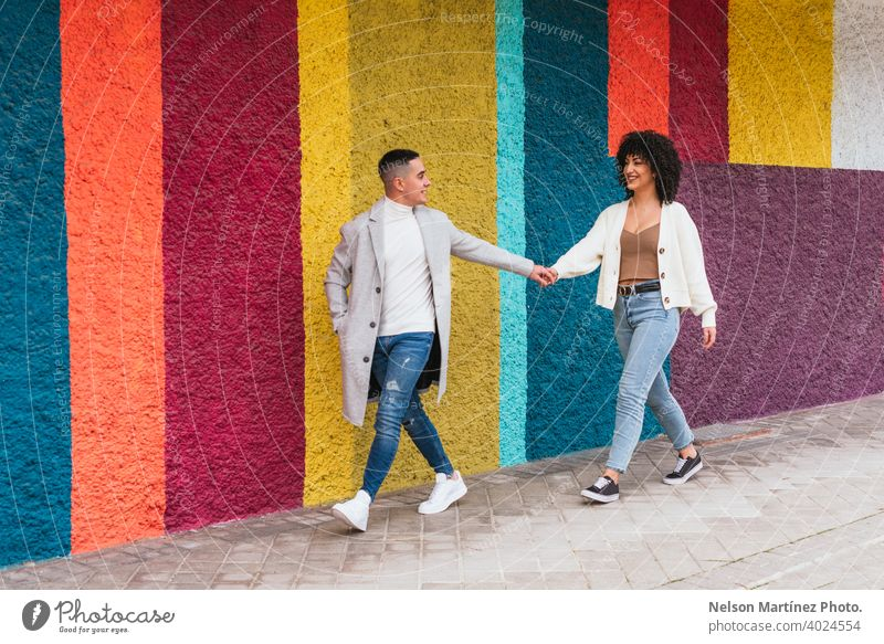 Young happy couple holding hands and walking through a pavement against a colorful wall stripes young love woman people together male relationship two happiness