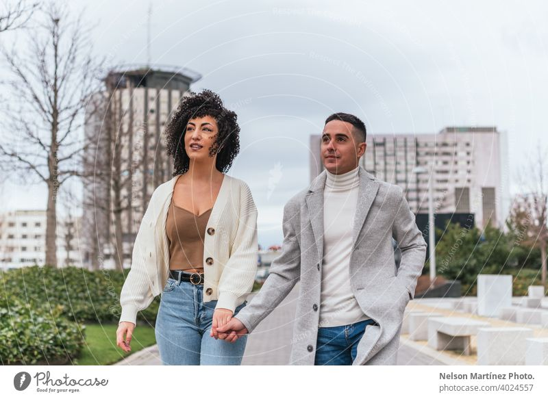 Shallow focus of a young couple holding hands and walking in a park under a cloudy sk shallow sky love woman people together male relationship happy two