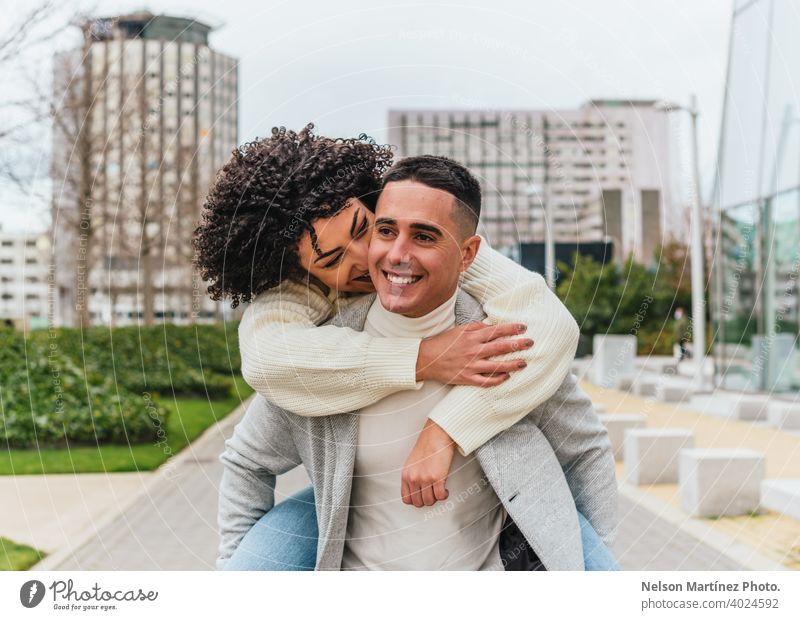 Shallow focus of a young smiling man carrying his girlfriend on his back cheerful couple shallow youth outdoors adult happy woman female people together person