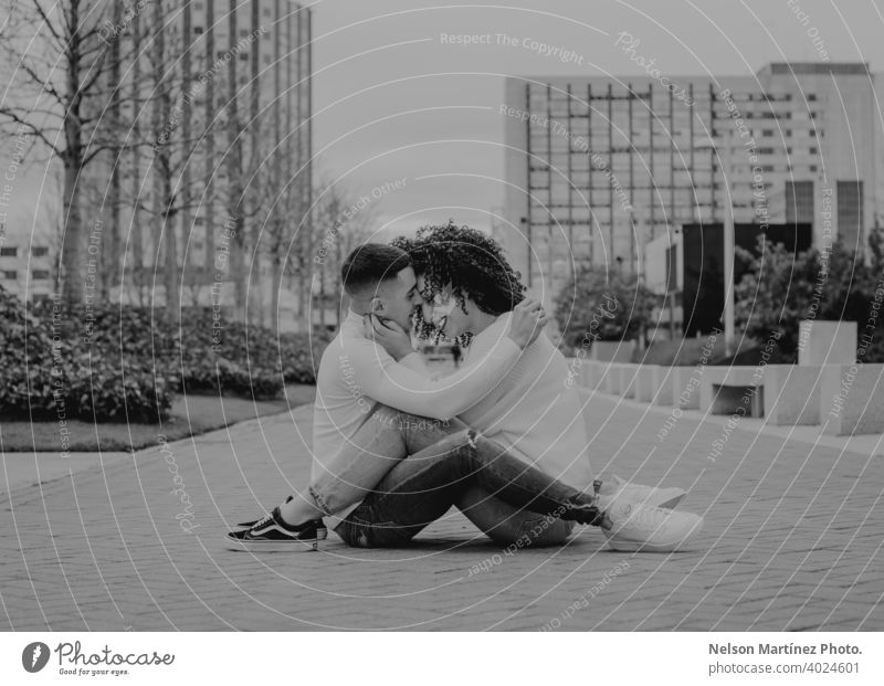 Black and white shallow focus of a romantic young couple kissing on a pavement under a cloudy sky outdoors woman romance together female happiness people adult