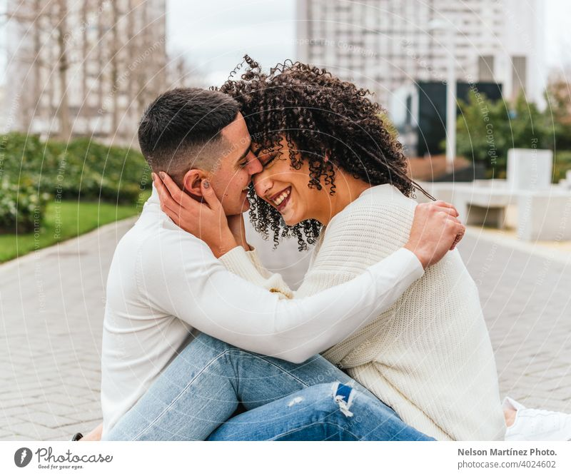 Shallow focus of a romantic young couple hugging on a pavement under a cloudy sky kissing outdoors shallow woman romance together female happiness people adult