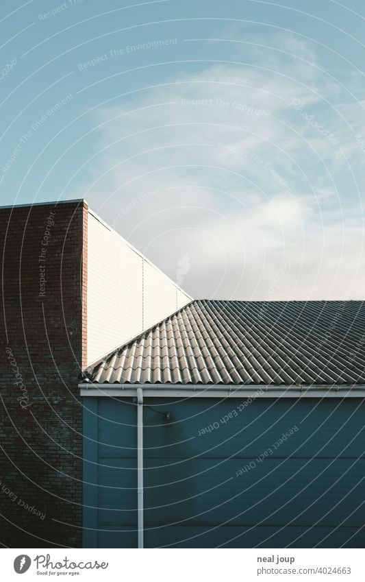 Geometric shapes where a corrugated metal roof meets a sunlit warehouse. Architecture Industry Economy minimalism Minimalistic Blue sky Gray Warehouse