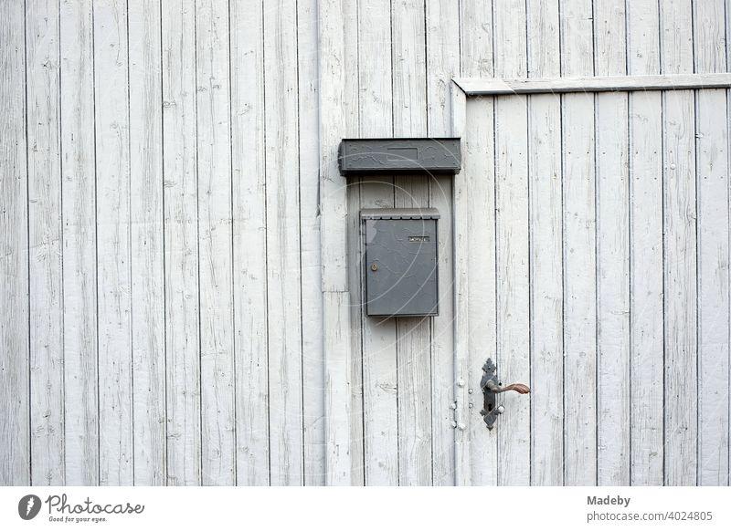 Entrance door in an old light grey wooden barn door of a farm in Wettenberg Krofdorf-Gleiberg near Giessen in Hesse, Germany Wooden gate Goal Barn Door