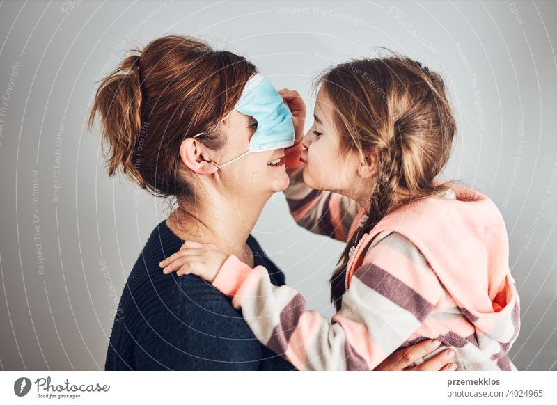 Little girl moving her mom's face mask on eyes and giving a kiss her mother. Funny moments during covid-19 pandemic affection affectionate bond care caucasian