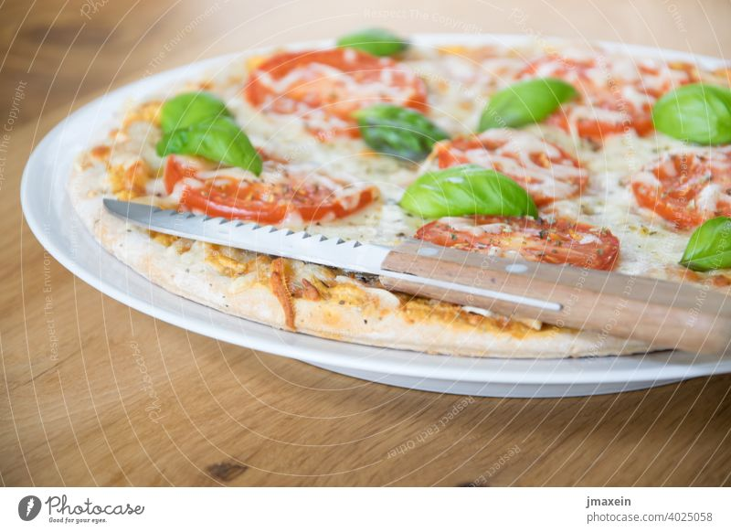 Pizza with knife pizza dough piece of pizza pizza service Eating Pizza Pizza slices Tomato Basil Cheese Mozzarella spices Italian Italy Wood Knives Table Plate