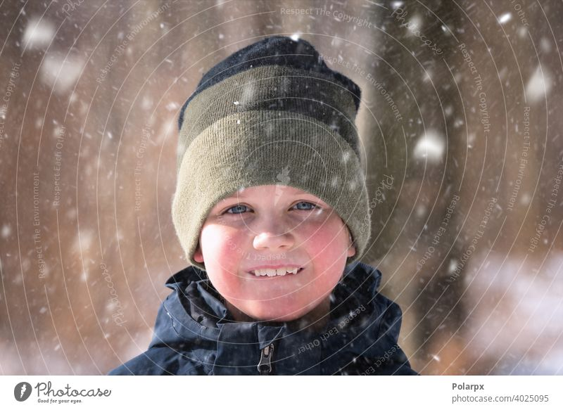 Young boy in the snow with a knitted hat natural wool clothes pretty environment closeup snowflake smiling lifestyle weather one freeze outdoors frost holiday
