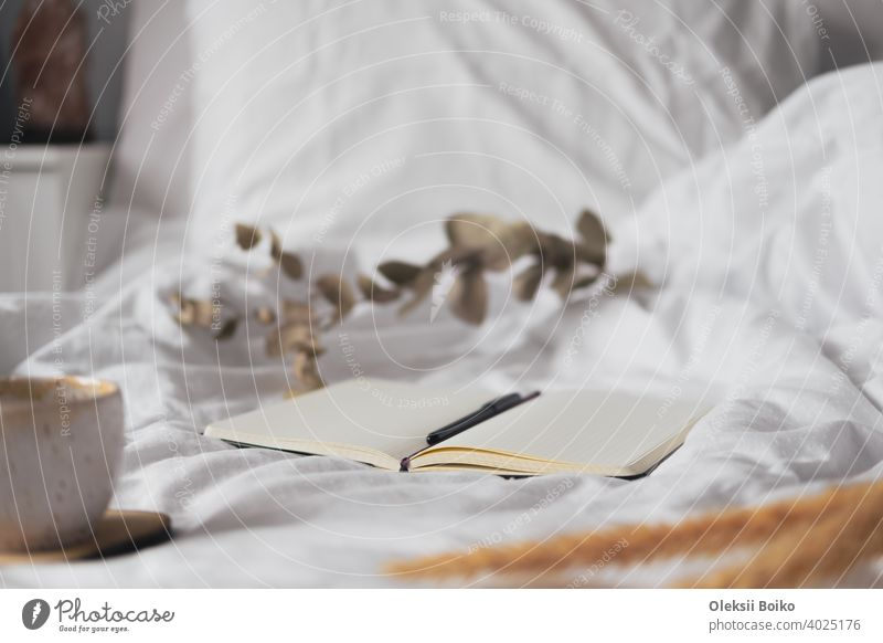 Open notepad with blank pages in textile white background, dried flowers and cup of tea. Tranquil and mindful home living, staying in bed, hand writing in a note book concept