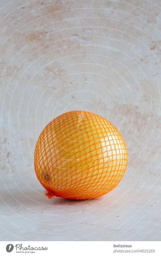 pomelo, single wrapped in a net and plastic foil on neutral background, vertical with copy space asian asian fruit citrus citrus maxima closeup delicious detox