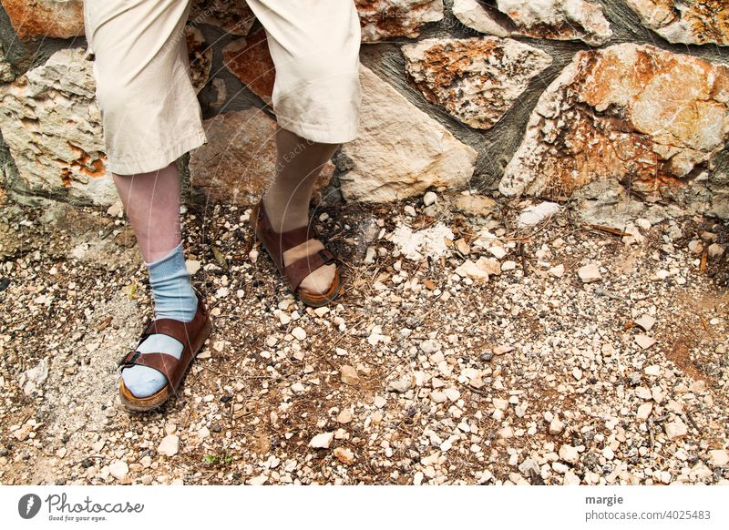 A man wears sandals with different socks Sandals Fashion Man Legs Feet Exterior shot Wall (barrier) Stony Footwear Curiosity stony road Human being Pants Adults