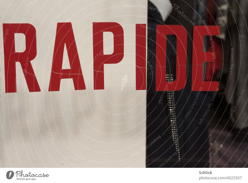 """""""RAPIDE"""" is written in French on a shop window in red capital letters, casting its drop shadow """"RAPID"""" translated into German on a white background Text"""