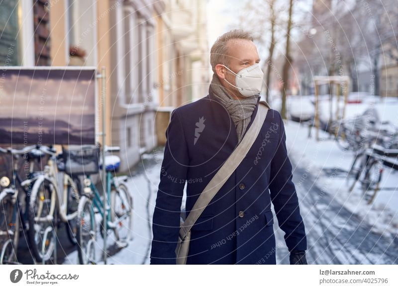 Man wearing a protective surgical face mask during the Covid-19 or coronavirus pandemic and winter overcoat with leather bag over his shoulder walking down a snowy urban street with parked bicycles in close up looking aside