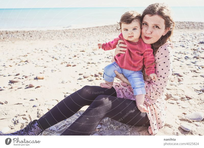 Happy family moment of a young mom enjoying a day on the beach with her baby love holidays happiness lifestyle sun sunny summer trendy fashion mother parenthood