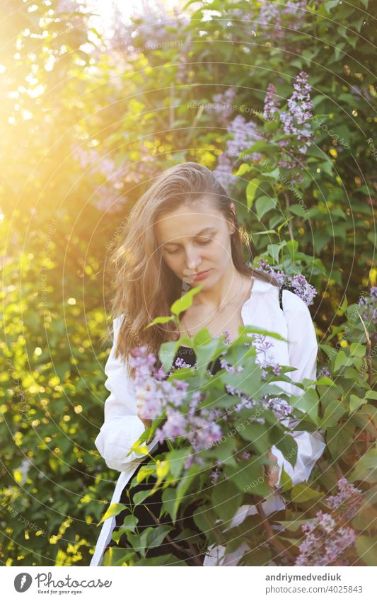 unreal stunning beautiful young woman walking in a green flowered in spring in a lavender garden with a bouquet of lilac in the hands. Closeup fashion romantic portrait. smelling the flowers
