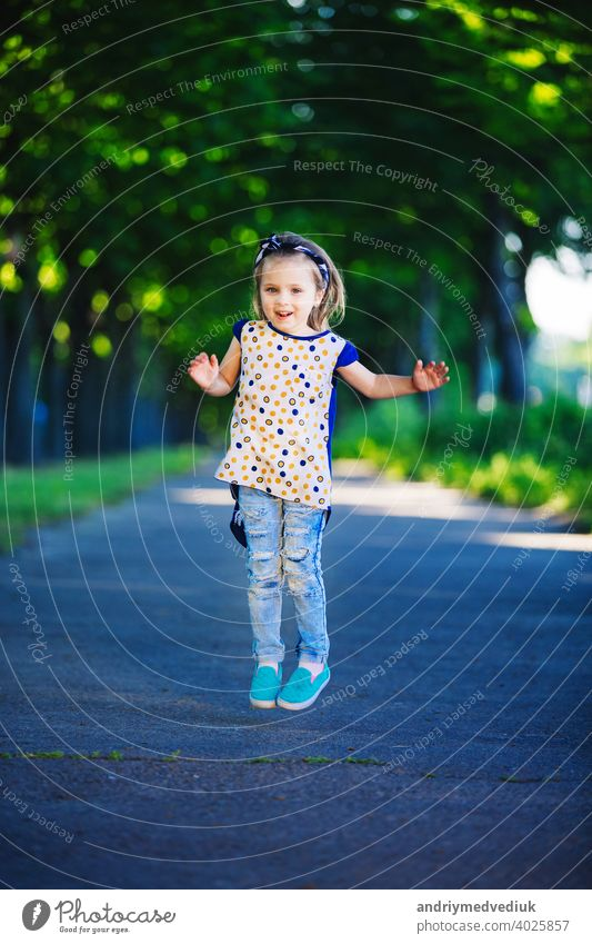 Cute little girl is having fun, jumping and laughing outdoors. happy childhood cute kid cheerful young lifestyle people person happiness park grass adorable