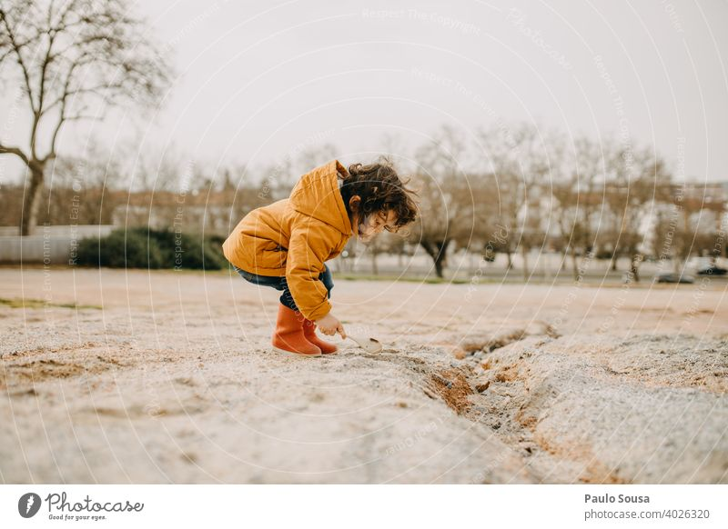 Side view of child with red rubber boots playing outdoors Red Child childhood Joy Infancy Childhood memory Toddler Boy (child) Happiness Colour photo